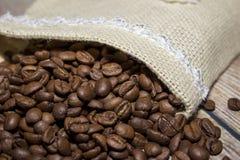Granos de café derramados fuera del bolso foto de archivo libre de regalías