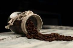 granos de café dispersados en un tarro en la madera Imagen de archivo libre de regalías