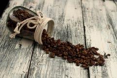 granos de café dispersados en un tarro en la madera Fotografía de archivo libre de regalías