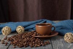 Granos de café dispersados, taza con la bebida, bolas de la cuerda, en el fondo de la tela Fotografía de archivo