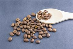 Granos de café dispersados de una cuchara de madera imagen de archivo libre de regalías