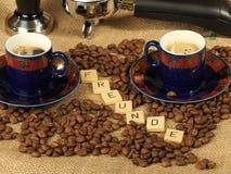 Granos de café, dos tazas adornadas, pisón y manija del grupo con las letras Freunde en un fondo de la arpillera Fotos de archivo