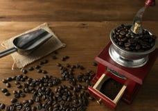 Granos de café en amoladora, en fondo de madera de la tabla Imagen de archivo
