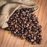 Granos de café en bolso sobre una tabla de madera Fotos de archivo