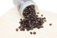 Granos de café en botella en el bloque de madera Imagen de archivo