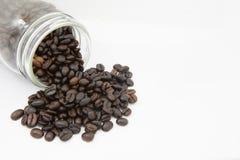 Granos de café en botella en el fondo blanco Foto de archivo