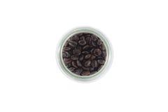 Granos de café en botella en el fondo blanco Foto de archivo libre de regalías