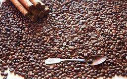 Granos de café en bulto con una cuchara vieja y varios cigarros Imagen de archivo libre de regalías