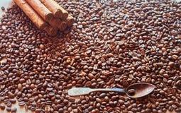 Granos de café en bulto con una cuchara vieja y varios cigarros Imágenes de archivo libres de regalías