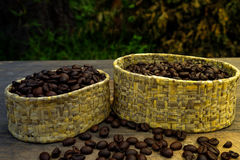 Granos de café en bulto en la tabla de madera y una luz suave foto de archivo libre de regalías