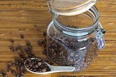 Granos de café en cuchara con el tarro de cristal fotos de archivo libres de regalías