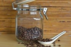 Granos de café en cuchara con el tarro de cristal Imagen de archivo libre de regalías