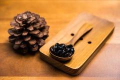 Granos de café en cuchara de madera Foto de archivo