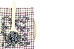 Granos de café en cuchara de madera en un mantel Imagen de archivo libre de regalías