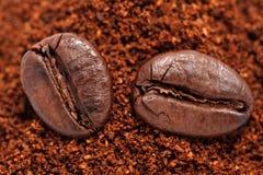 Granos de café en el café molido Imágenes de archivo libres de regalías