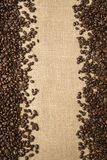Granos de café en el fondo de las telas del yute fotografía de archivo