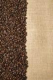 Granos de café en el fondo de las telas del yute Imagen de archivo libre de regalías