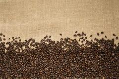 Granos de café en el fondo de las telas del yute Fotos de archivo libres de regalías