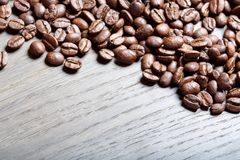 Granos de café en el fondo de madera marrón imagen de archivo