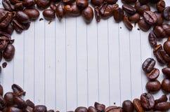 Granos de café en el papel para las notas imagen de archivo