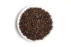 Granos de café en el platillo blanco Imagen de archivo