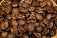 Granos de café en el platillo de madera Fotografía de archivo