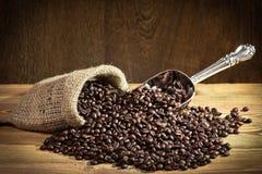 Granos de café en el saco de la arpillera con la cucharada del metal Fotografía de archivo