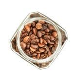 Granos de café en el tarro de cristal aislado en el fondo blanco Visión superior foto de archivo