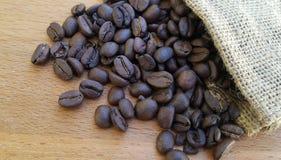 Granos de café en fondo de madera Imagenes de archivo