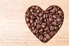 Granos de café en forma de corazón en el tablero de madera Imágenes de archivo libres de regalías