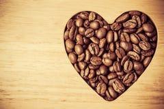 Granos de café en forma de corazón en el tablero de madera Fotografía de archivo libre de regalías