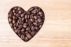 Granos de café en forma de corazón en el tablero de madera Fotografía de archivo