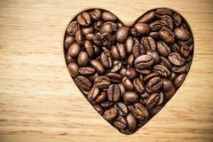 Granos de café en forma de corazón en el tablero de madera Imagenes de archivo