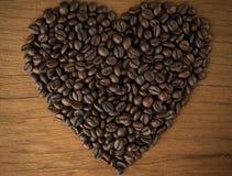 Granos de café en forma de corazón en los viejos tableros de madera Imagenes de archivo