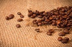Granos de café en harpillera Imagenes de archivo