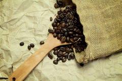 Granos de café en la cuchara de madera en saco de la arpillera en backg del papel marrón Foto de archivo