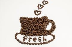 Granos de café en la dimensión de una variable de una taza y de un platillo Foto de archivo libre de regalías
