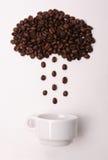 Granos de café en la forma de la lluvia de colada de la nube en una taza blanca en el fondo blanco Foto de archivo