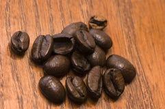 Granos de café en la madera roja Foto de archivo libre de regalías