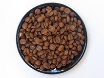 Granos de café en la placa sobre el fondo blanco Fotografía de archivo