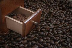 Granos de café en la tabla con el polvo en amoladora de café Imagenes de archivo