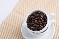 Granos de café en la taza blanca Foto de archivo