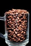 Granos de café en la taza vidriosa, cierre para arriba, en un oscuro imagen de archivo libre de regalías
