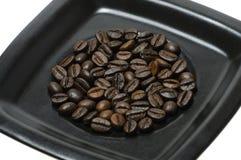 Granos de café en plato Imágenes de archivo libres de regalías