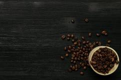 Granos de café en pote de madera en la tabla de madera negra imagen de archivo