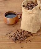 Granos de café en saco y taza Foto de archivo libre de regalías
