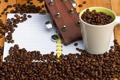 granos de café en taza con la guitarra y habas en el cuaderno en blanco Foto de archivo