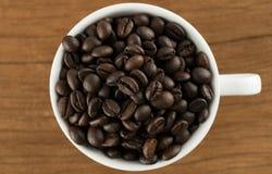 Granos de café en taza de café en fondo de madera de la tabla Imágenes de archivo libres de regalías