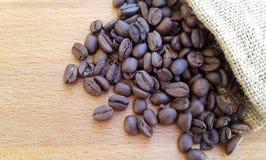 Granos de café en un bolso en fondo de madera Imagen de archivo libre de regalías