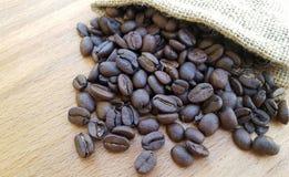 Granos de café en un bolso en fondo de madera Imágenes de archivo libres de regalías